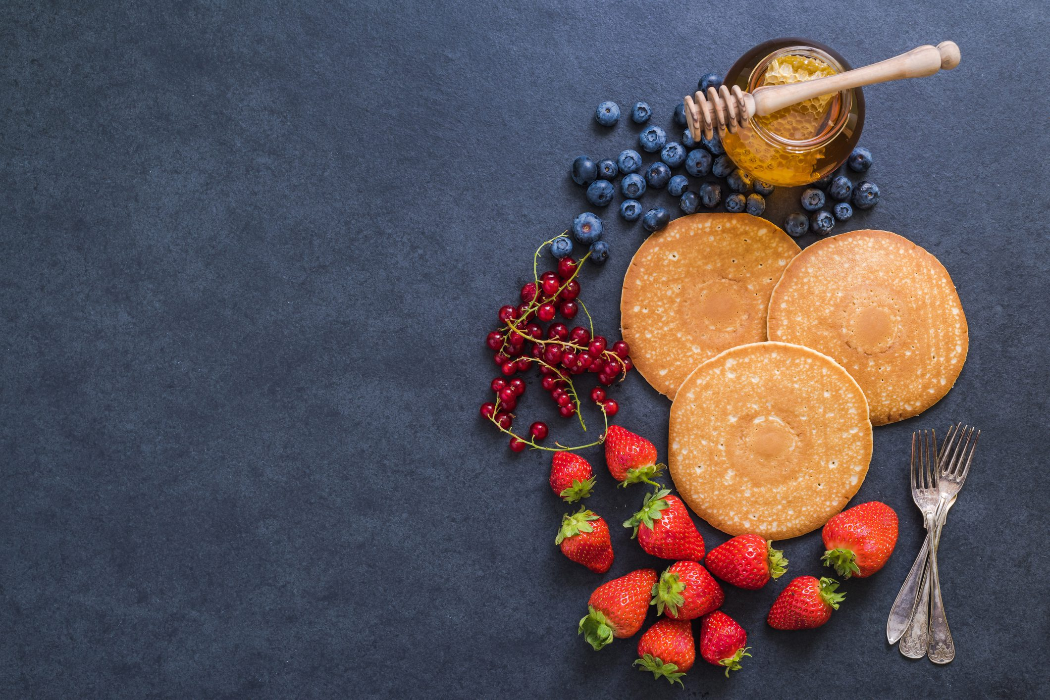 pancakes surrounded by fruit and honey