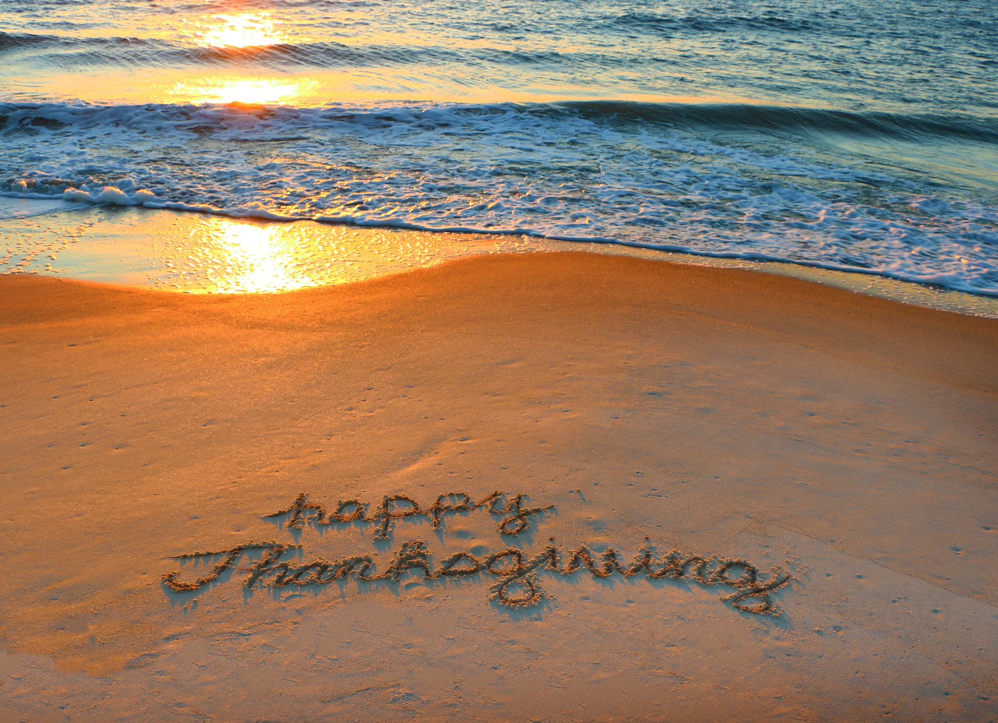 Happy Thanksgiving written in sand at the beach