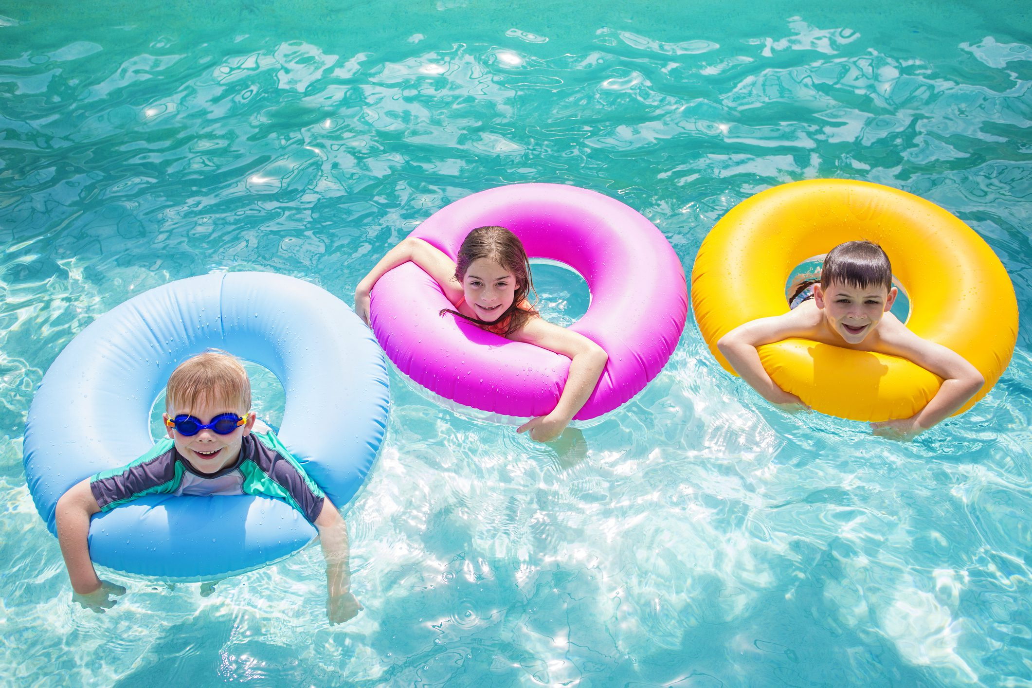 three children using floats in pool