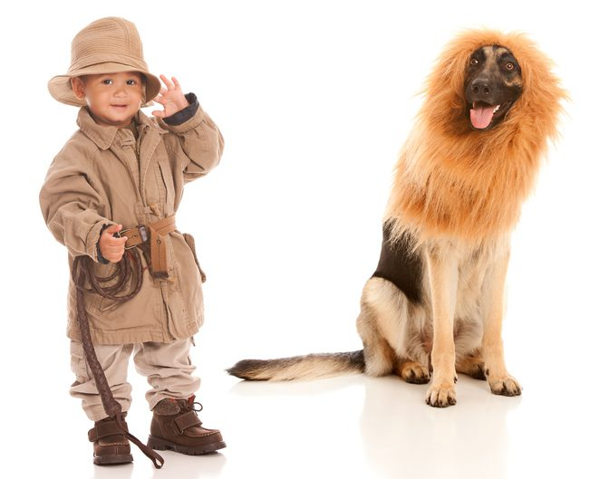 Kid dressed as zoo keeper and dog dressed as lion