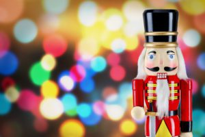 Soldier nutcracker statue standing in front of bright Christmas lights