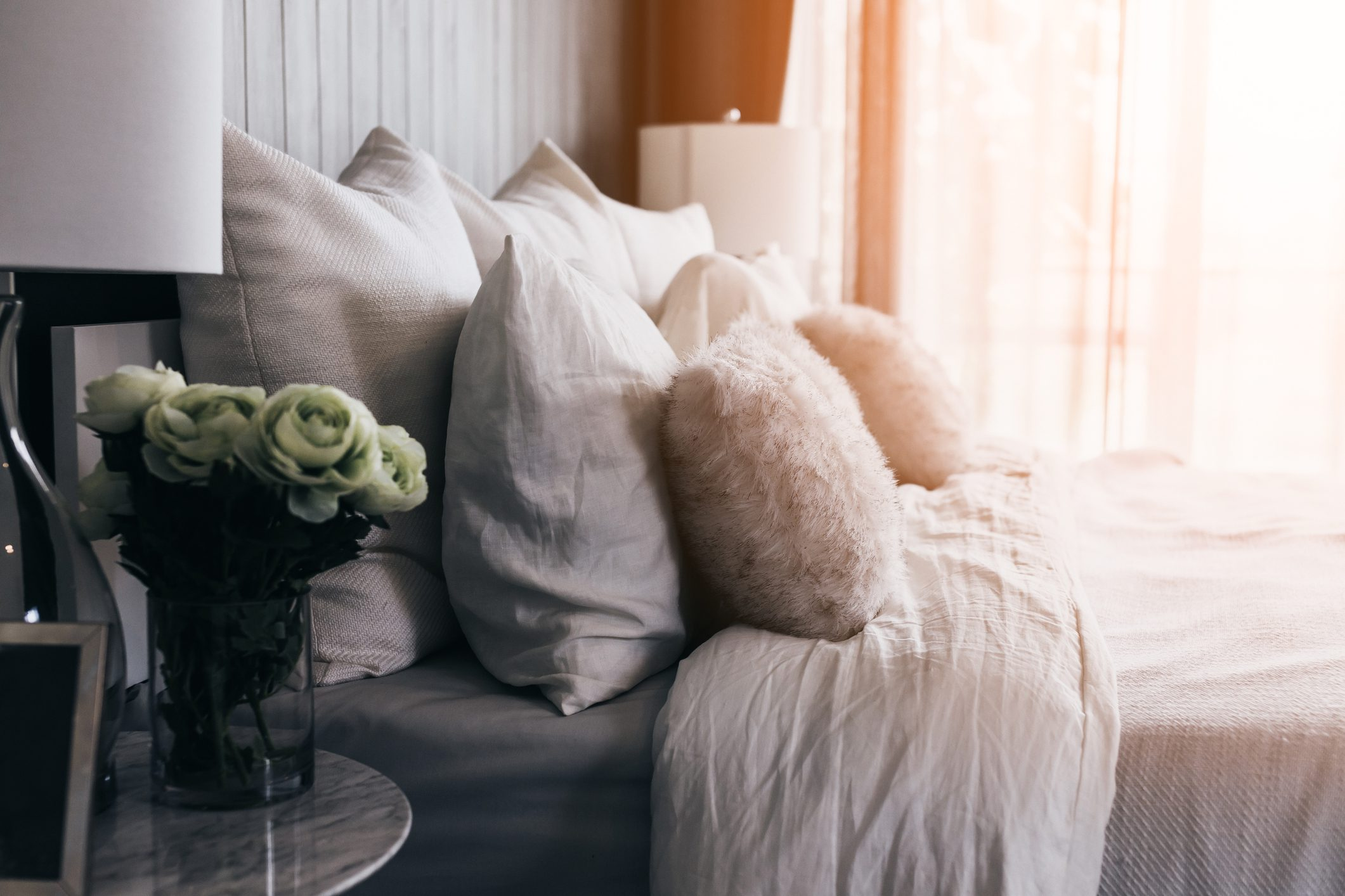 light soft pillow on beautiful bed cozy bedroom with sun light from window interior concept