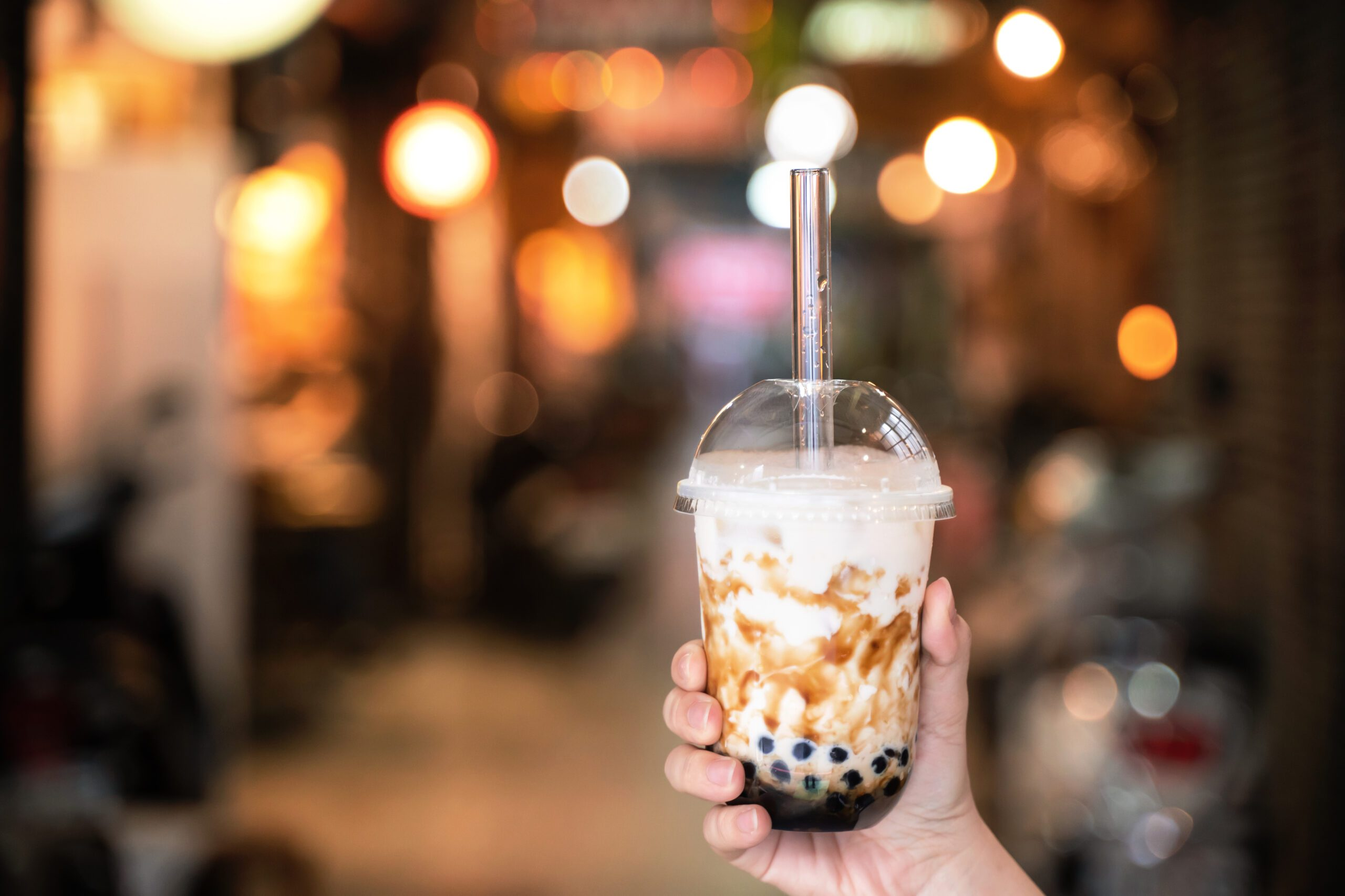 Brown sugar flavored bubble tea with a glass straw