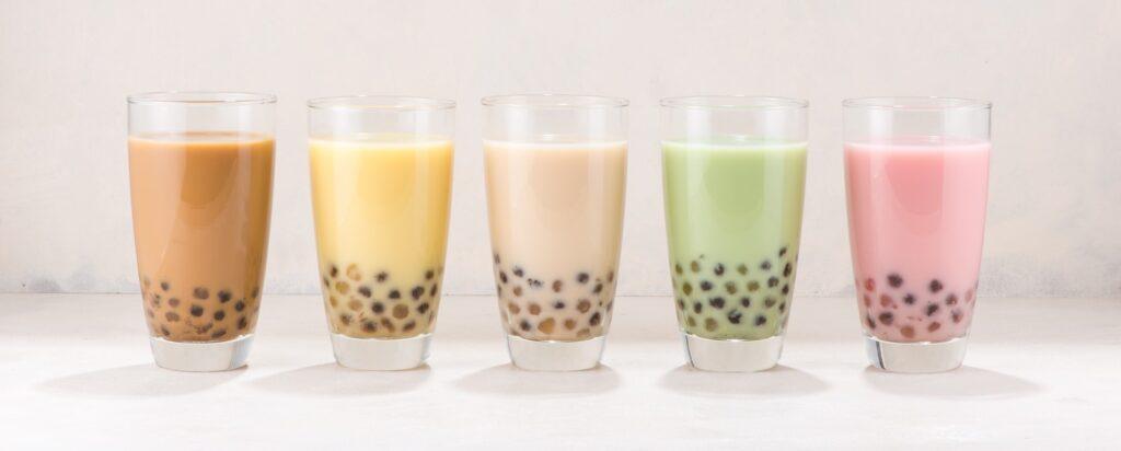 Row of fresh boba bubble tea glasses on white background.