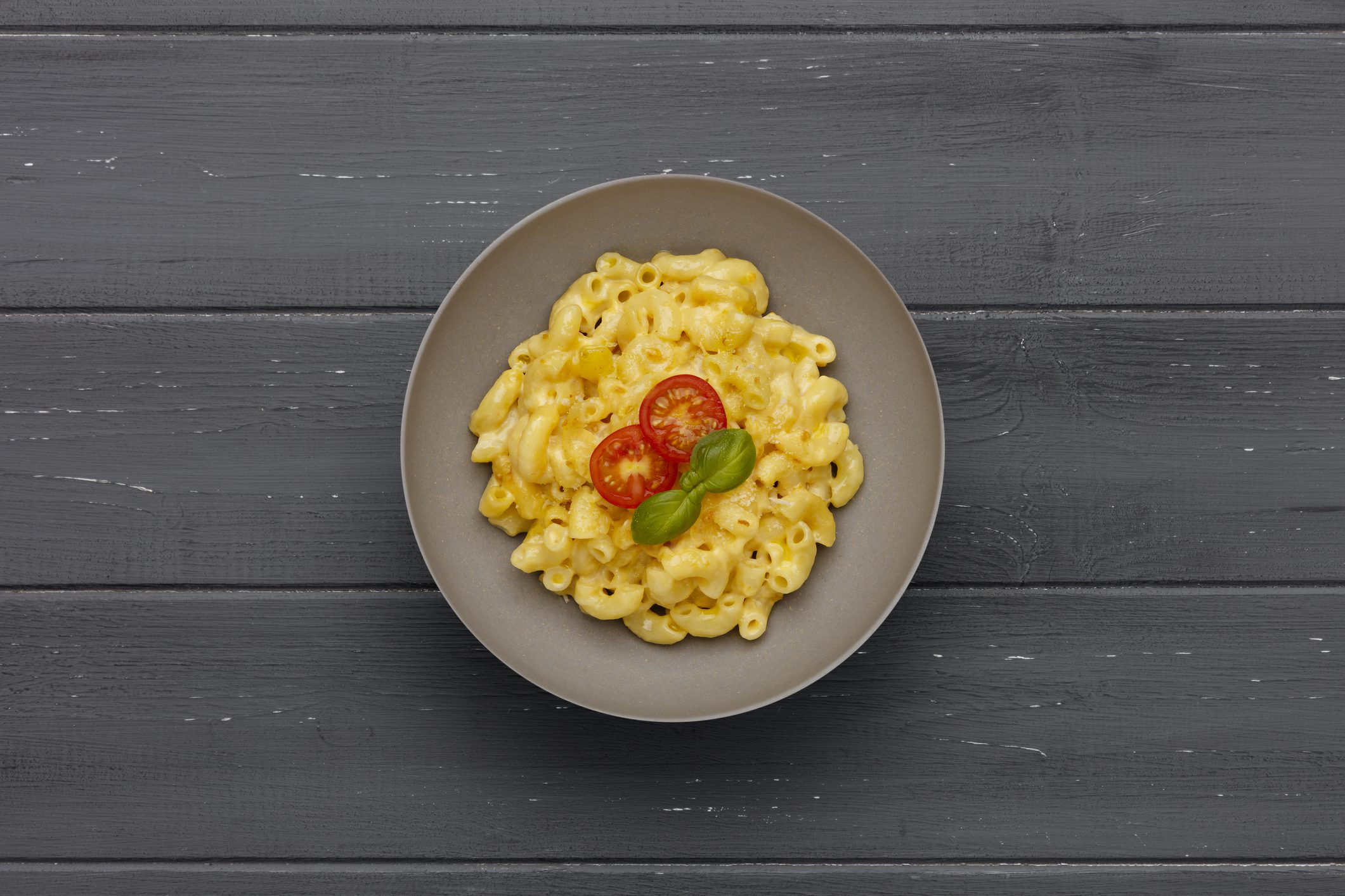 A bowl of delicious Macaroni and cheese, topped with cherry tomatoes and basil, on a distressed wooden background.