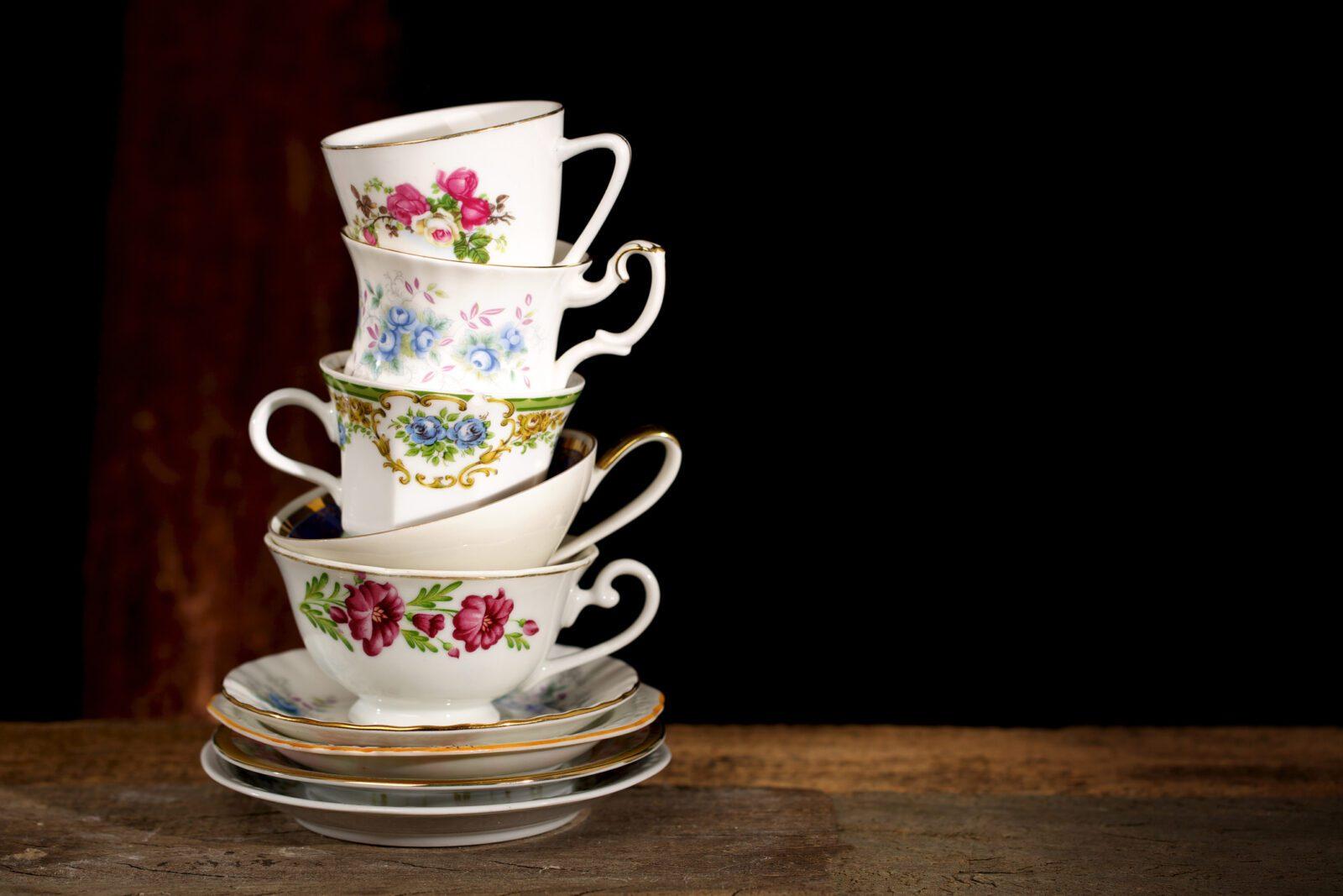 Various vintage porcelain teacups with floral decoration on dark background.